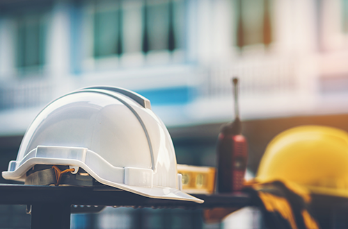White and yellow hard hats with construction gloves and radio